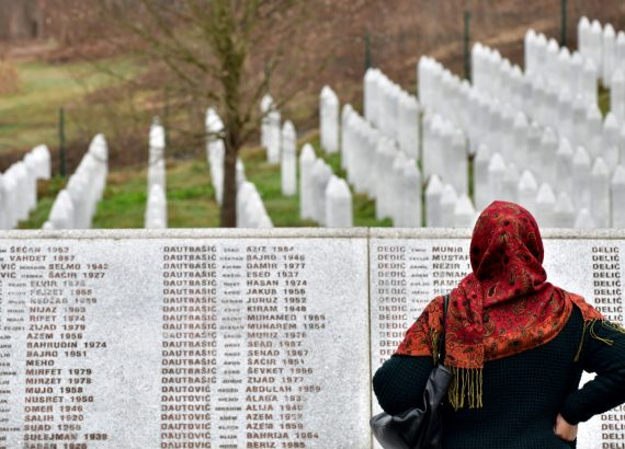 A Bosnian Muslim woman walks by the memorial wall containing the names of the victims at the Srebrenica memorial in Potocari [2019]/ Elvis Barukcic/ AFP via Getty Images